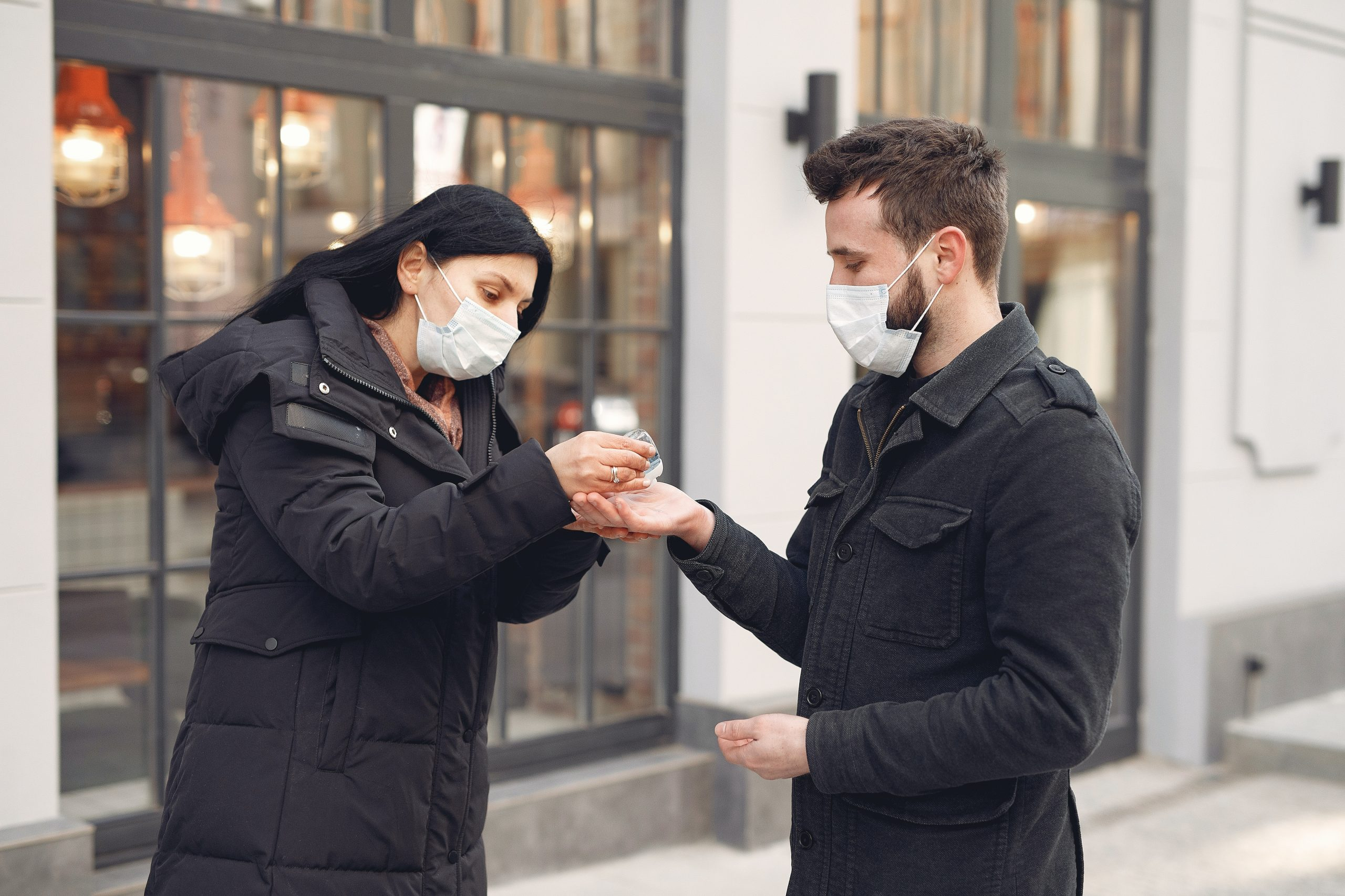 woman putting hand sanitizer on man s hand 3983406