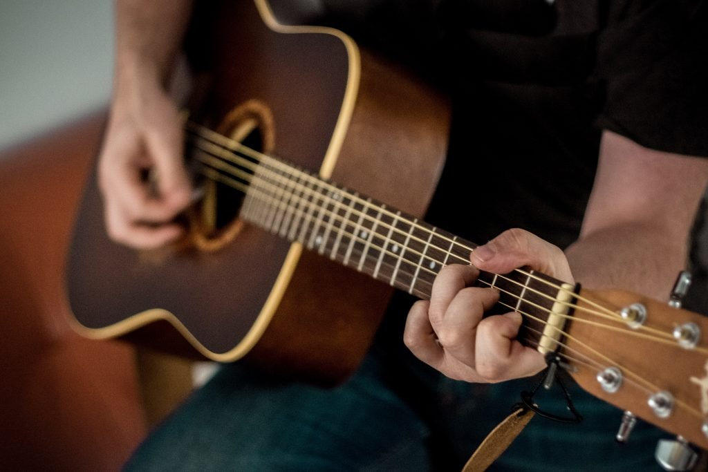 person playing brown guitar 1407322