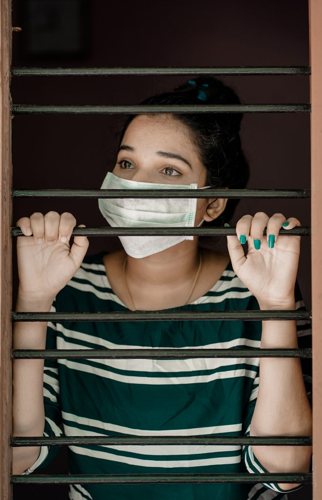 woman in green and white stripe shirt covering her face with 3991311